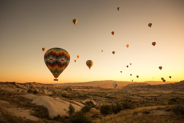 トルコ、カッパドキアの地上を飛んでいる色付きの風船のセット 無料写真