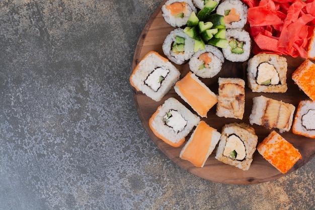 나무 접시에 맛있는 다른 초밥 세트 무료 사진