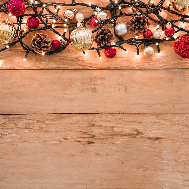 Set of different Christmas balls between fairy lights Free Photo