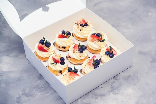 Набор различных вкусных кексов. бумажная коробка с фруктовыми кексами. праздничные кексы с клубникой и черникой. Premium Фотографии