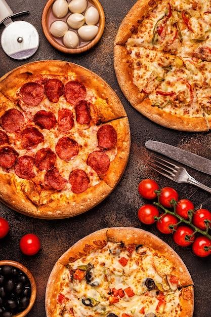 さまざまなピザ-ペパロニ、ベジタリアン、チキンと野菜のセット Premium写真