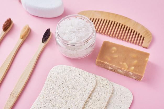 Набор экологически чистых предметов личной гигиены на розовой поверхности. бамбуковая зубная щетка, деревянная расческа, губка, мыло и морская соль, вид сверху, плоская планировка. ноль отходов концепция Premium Фотографии