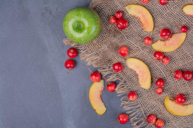 Набор фруктов. яблоко, вишня и дольки персика на синем. Бесплатные Фотографии