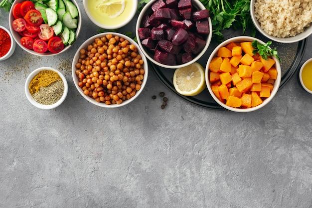 料理のための健康的なベジタリアン食材のセット。香辛料入りのヒヨコ豆、焼きカボチャとビート、キノアと野菜。 Premium写真
