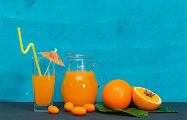 シアンの織り目加工の表面にガラス、葉、オレンジのジュースのセットです。側面図。 無料写真