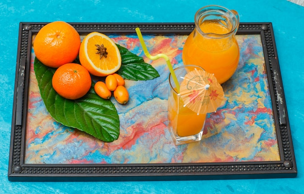 メガネ、葉、マンダリンオレンジ、シアンの抽象的な色のフレームにオレンジのジュースのセット。ハイアングル。 無料写真