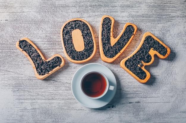 お茶と白い木製の背景にお茶で満たされた愛のテキストのセット。上面図。 無料写真