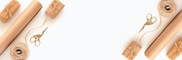 명절 선물 포장 재료 세트. 크래프트 종이, 황마 꼬기, 가위, 흰색 배경에 상자로 만든 배너. 프리미엄 사진