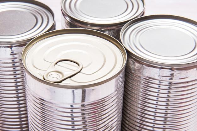 Набор металлических консервных банок на деревянный стол Premium Фотографии