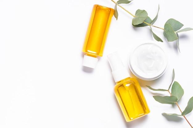 Набор органических эфирных масел и свежих ароматных листьев эвкалипта на белом фоне Premium Фотографии