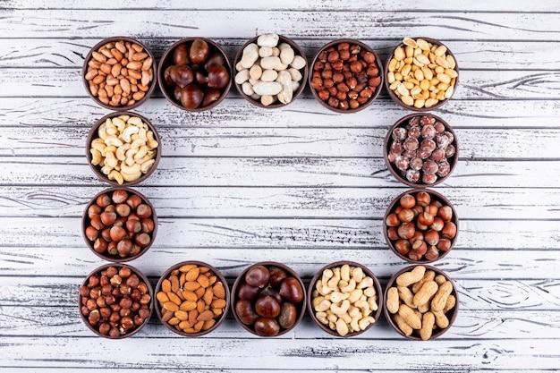 ピーカンナッツ、ピスタチオ、アーモンド、ピーナッツ、ナッツの盛り合わせ、ドライフルーツの長方形の形をした白い木製のテーブルにミニの異なるボウル 無料写真