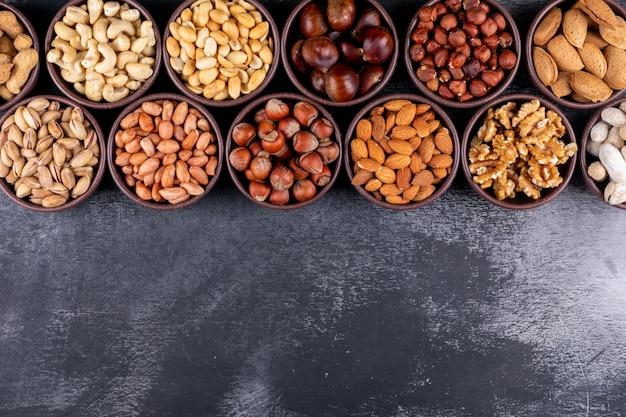 ピーカン、ピスタチオ、アーモンド、ピーナッツのセット、ナッツの盛り合わせとドライフルーツをミニボウルに並べて 無料写真