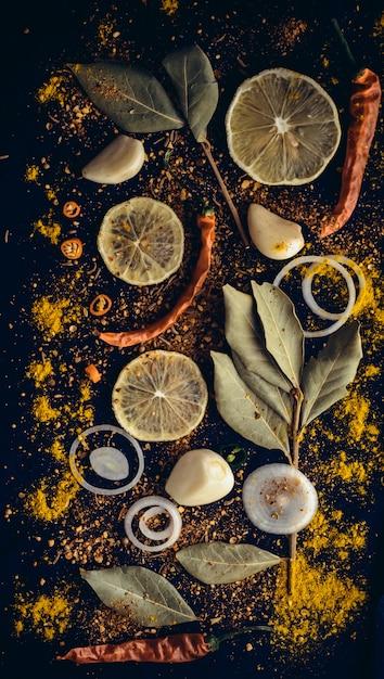 スパイスのセット:タマネギ、レモン、ニンニク、赤唐辛子、パプリカ、黒胡pepper、キャラウェイシード、クミン、カレー、ローレルリー、ターメリック、ウコン。 Premium写真