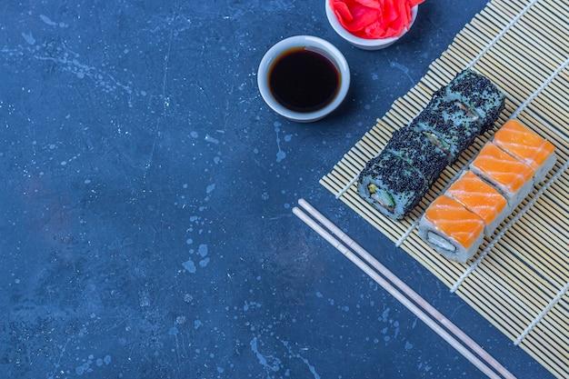 サーモンとオムレツ、豆腐、野菜、トビウオの卵、暗いテーブルの上の巻きakiの天ぷら巻き寿司のセット。伝統的な日本食。コピースペース。平面図、平置き Premium写真
