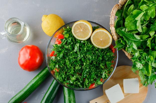 Набор из помидоров, сыра, лимона, огурца и рубленой зелени в стеклянной посуде на серой поверхности Бесплатные Фотографии