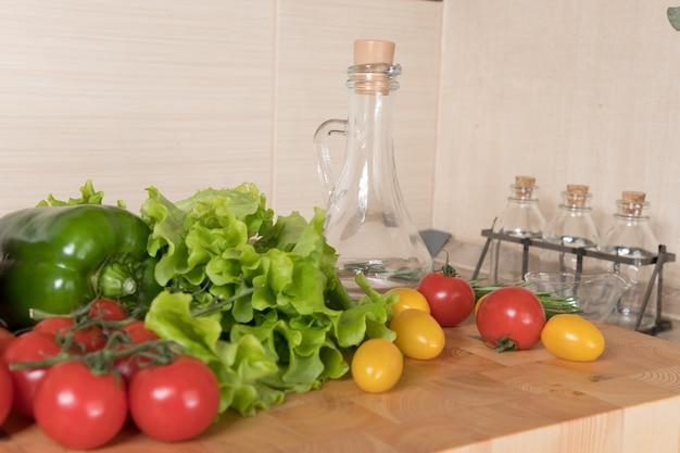キッチンのまな板にさまざまな野菜のセット。健康的な食事の概念。サラダの材料、トマト、唐辛子、オリーブオイル、スパイス Premium写真