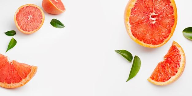 全体とカットフレッシュグレープフルーツとスライスの白い表面に分離 無料写真