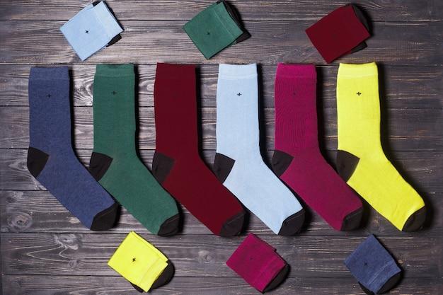Набор зимних повседневных цветных носков, плоских на деревянном фоне Premium Фотографии
