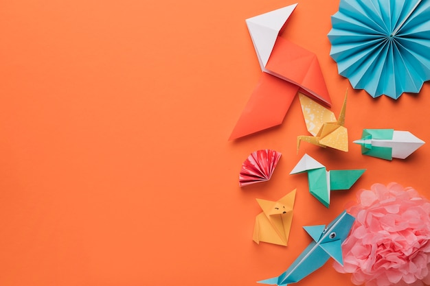 Set of origami paper art craft on bright orange surface Free Photo