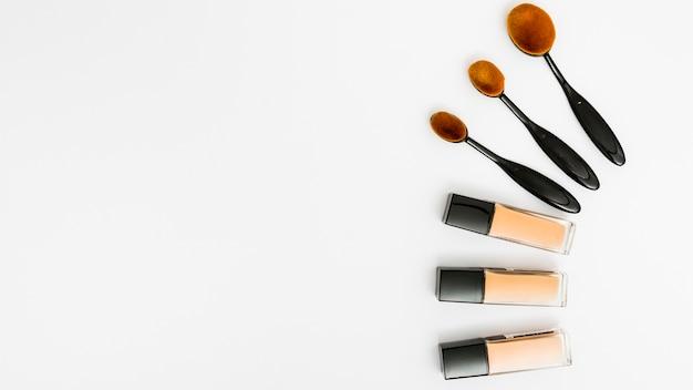 Set of oval makeup brushes with liquid foundation bottles on white backdrop Premium Photo