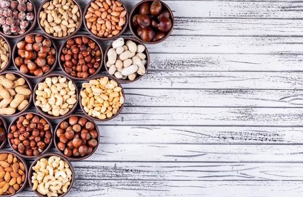 Set of pecan, pistachios, almond, peanut, and assorted nuts and dried fruits in a cycle shaped mini different bowls on a white wooden table Free Photo