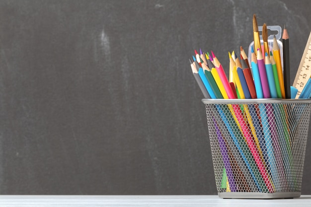 A set of pencils, brushes, paints on the background of the school board. Premium Photo