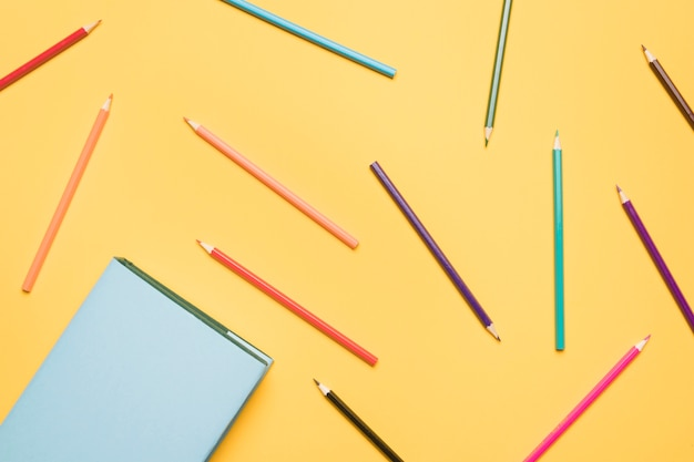 Set of pencils scattered on yellow background Free Photo