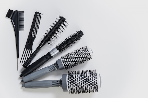 Set of professional hairbrushes on white background in hair salon Premium Photo