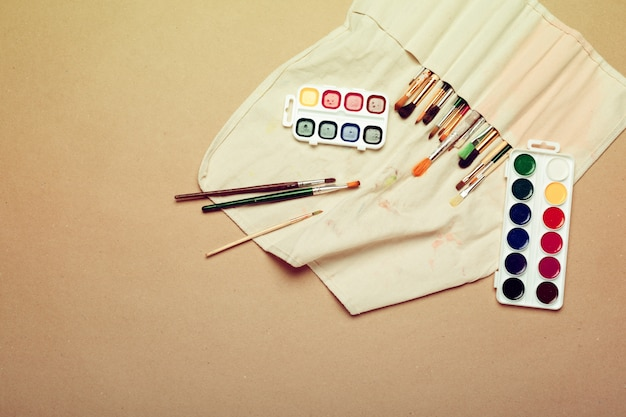 Set of professional watercolor artist brushes in a hand made roll case and watercolor paints close up Premium Photo