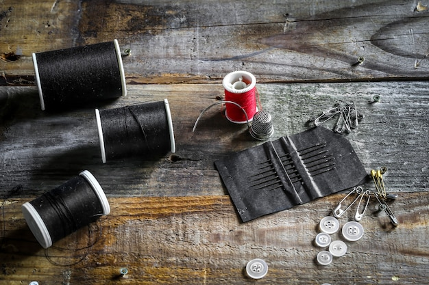 Set of sewing threads and accessories on wooden wall Free Photo