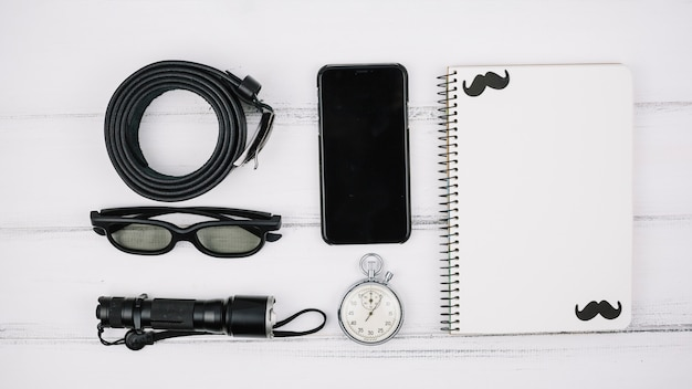 Set of smartphone near notebook and male accessories Free Photo