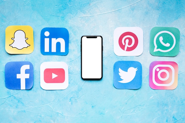 Set of social networking icons placed near smartphone Free Photo