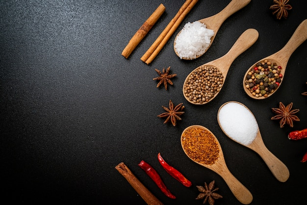 A set of spices and herbs with spoon and copy space on black Premium Photo
