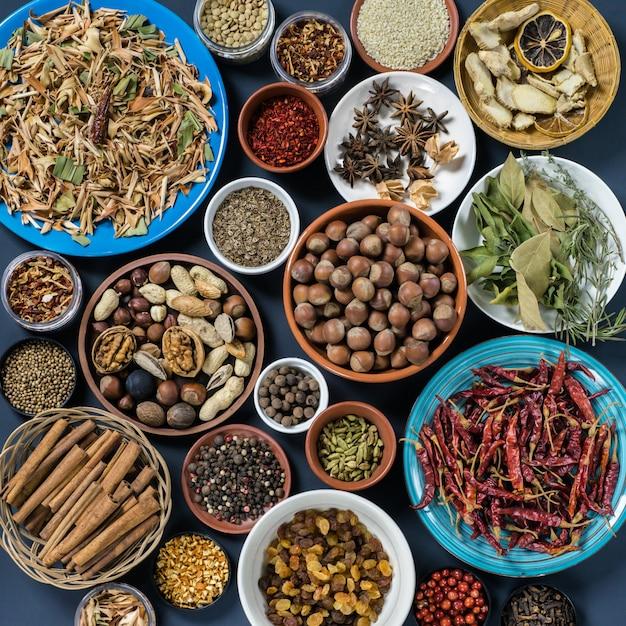 Set of spices and nuts: lemon grass, cinnamon, pepper, anise, rosemary, laurel leaf, ginger, hazel-nut, walnut, almond, coriander, badyan. Premium Photo