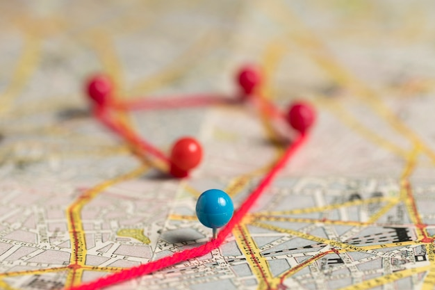 Set of stationery pins and thread on map high view Free Photo