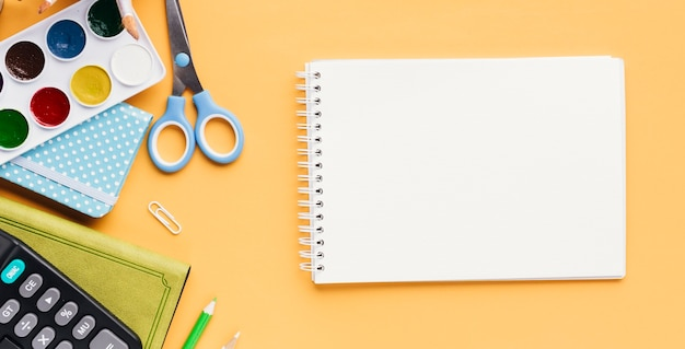 Set of stationery next to sketch pad Free Photo