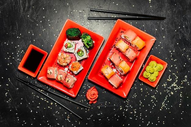 Set of sushi, japanese knife, chopsticks and on dark stone table. Free Photo