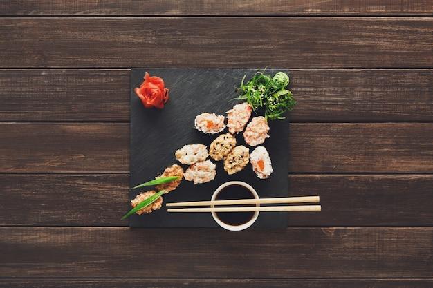 Set of sushi maki and rolls on black rustic wood Premium Photo
