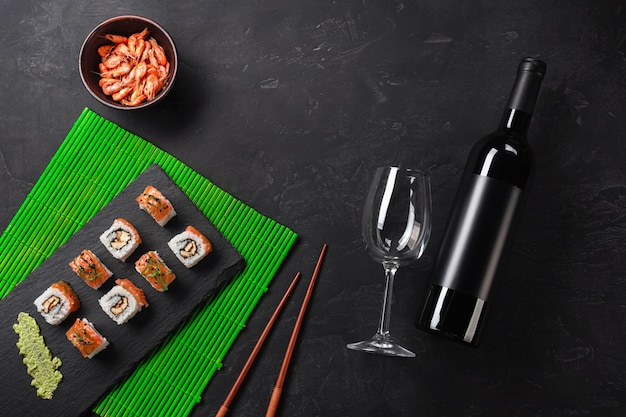 Set of sushi and maki with a bottle of wine on stone table. top view with copy space Premium Photo