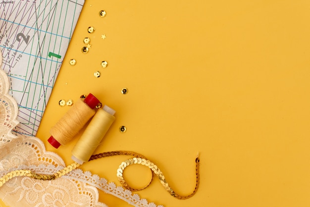 Set of tailoring accessories on grey background, top view Premium Photo
