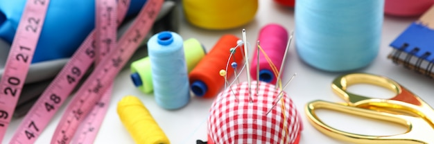 Set of threads and needles lying at worktable Premium Photo