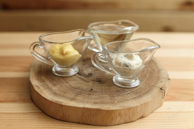 Set of three transparent sauceboats with different sauces on wooden plate Premium Photo