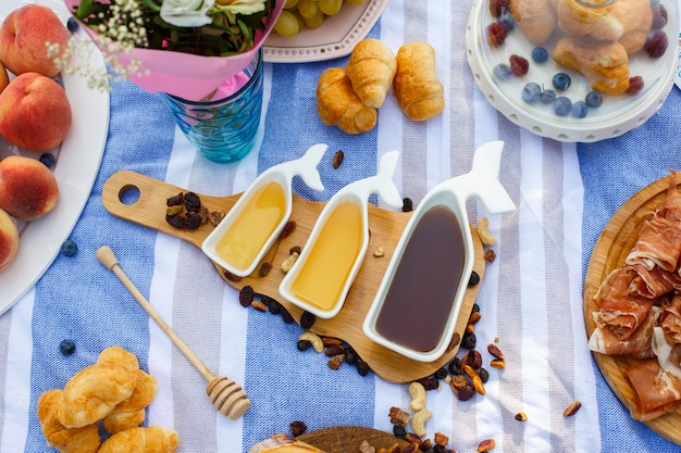 Set of three white sauceboats with sweet honey on wooden tray at picnic food lay out background Premium Photo