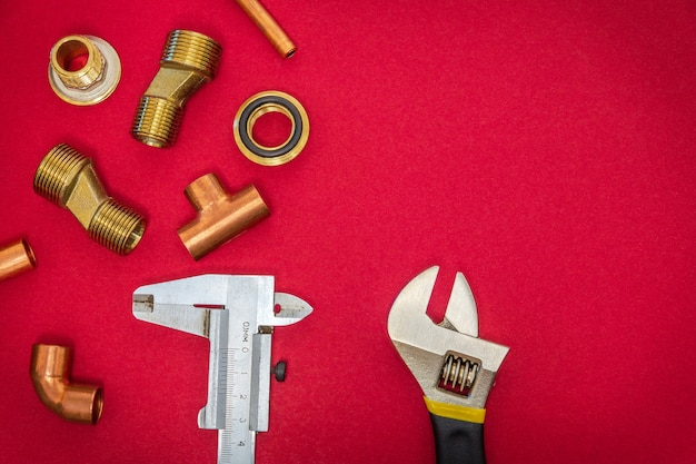 Set of tools and spare parts for plumbingon red background Premium Photo
