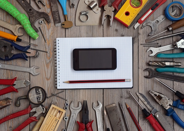 Set of tools on a wooden floor with a notebook and a mobile phone in the centre. Premium Photo