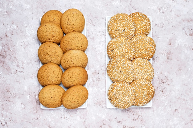 Set of various american style cookies on a light concrete background. shortbread with confetti, sesame seed, peanut butter, oatmeal and chocolate chip cookies. Free Photo
