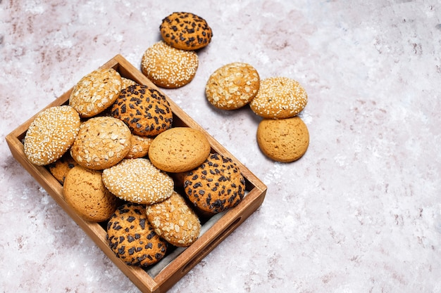 Set of various american style cookies in wooden tray on light concrete background. shortbread with sesame seed, peanut butter, oatmeal and chocolate chip cookies. Free Photo