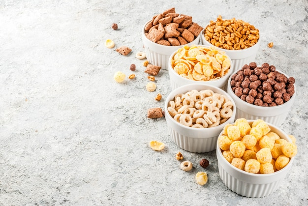 Set of various breakfast cereal corn flakes, puffs, pops Premium Photo