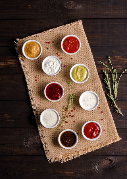Set of various portioned sauces on a dark wooden rustic background. low key. Premium Photo
