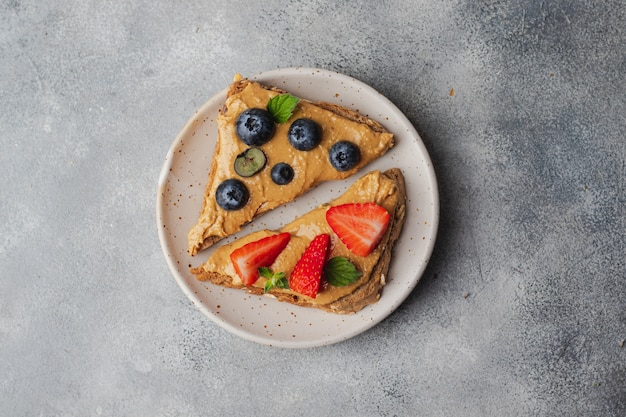 Set of various toast with peanut butter; honey; mint; peanut, blueberry and strawberry Premium Photo
